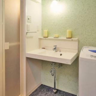 壁に丸いグリーンのモザイクタイルを採用し、清潔感を演出。