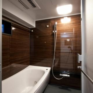 浴室を濃いブラウンの木目調の壁パネルで統一。